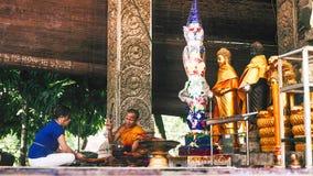 Het aanbieden van ceremonie in boeddhistische tempel tussen vrouwen en monnik Stock Foto's