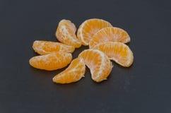 Het aandeel van Mandarin in de vorm van een cirkel op zwarte bedelaars Royalty-vrije Stock Foto's