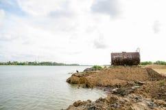 Het aangetaste en roestige vat van de olieopslag door het water tegen beaut Royalty-vrije Stock Foto