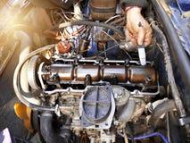 Het aanhalen van de kleppen met een auto-illuminator in de garage in een oude auto royalty-vrije stock afbeeldingen