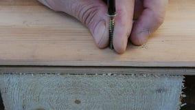 Het aanhalen van de schroeven in het hout om meubilair te bouwen stock footage