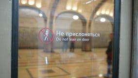 Het aankomen bij metro post Mayakovskaya in Moskou De mening van de glasdeur van de metro met etiket ` leunt niet op deur stock videobeelden