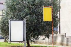Het aanplakbord en de gele advertentie schepen in de straatstad, de groene installaties, de selectieve nadruk en de close-up in L royalty-vrije stock afbeeldingen