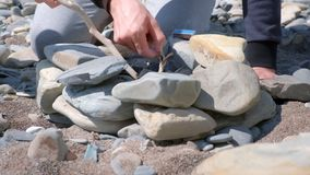 Het aansteken van de steenkolen in het vuur op de met de hand gemaakte stenenkoperslager op overzees strand Familie het kamperen stock video