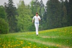 Het aanstoten - sportieve vrouw die in park loopt Stock Afbeeldingen