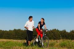Het aanstoten van de man en van de vrouw en met fiets Stock Fotografie