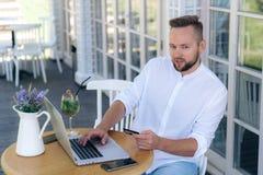 Het aantrekkelijk modieus jonge mensenwerk in een koffie, verricht betalingen van een betaalpas op Internet, gebruikt laptop en a stock fotografie