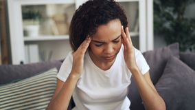 Het aantrekkelijke Afrikaanse Amerikaanse meisje lijdt aan hoofdpijn wat betreft haar hoofd het masseren tempels thuis binnen zit stock videobeelden