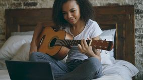 Het aantrekkelijke Afrikaanse Amerikaanse tienermeisje concentraing leren om gitaar te spelen die laptop computerzitting op bed g Royalty-vrije Stock Afbeeldingen