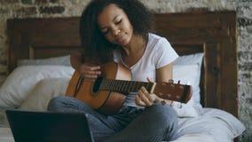 Het aantrekkelijke Afrikaanse Amerikaanse tienermeisje concentraing leren om gitaar te spelen die laptop computerzitting op bed g Royalty-vrije Stock Foto's