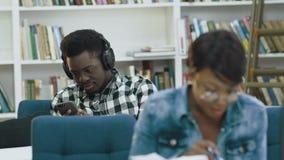 Het aantrekkelijke Afrikaanse vrouwelijke boek van de studentenlezing in de moderne bibliotheek terwijl Afrikaanse mannelijke stu stock videobeelden