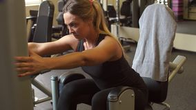 Het aantrekkelijke atletische meisje leidt haar benen op een simulator in de gymnastiek op stock footage