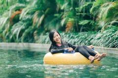 Het aantrekkelijke Aziatische vrouw ontspannen bij rivierpool stock fotografie