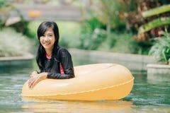 Het aantrekkelijke Aziatische vrouw ontspannen bij rivierpool stock foto's