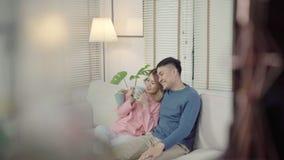 Het aantrekkelijke Aziatische zoete paar geniet liefde van ogenblik drinkend warme kop van koffie of thee in hun handen op bank i stock footage