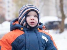 Het aantrekkelijke babyjongen spelen met de eerste sneeuw Hij glimlacht en kijkt sneeuwman Dik blauw-oranje jumpsuit heldere gest Royalty-vrije Stock Afbeeldingen