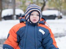 Het aantrekkelijke babyjongen spelen met de eerste sneeuw Hij glimlacht en kijkt sneeuwman Dik blauw-oranje jumpsuit heldere gest Stock Foto