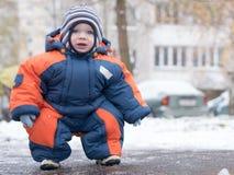 Het aantrekkelijke babyjongen spelen met de eerste sneeuw Hij glimlacht en kijkt sneeuwman Dik blauw-oranje jumpsuit heldere gest Royalty-vrije Stock Afbeelding