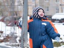 Het aantrekkelijke babyjongen spelen met de eerste sneeuw Hij glimlacht en kijkt sneeuwman Dik blauw-oranje jumpsuit heldere gest Royalty-vrije Stock Fotografie