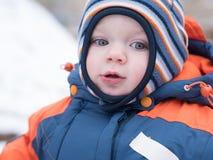 Het aantrekkelijke babyjongen spelen met de eerste sneeuw Hij glimlacht en kijkt sneeuwman Dik blauw-oranje jumpsuit heldere gest stock afbeeldingen
