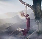 Het aantrekkelijke blonde dame hangen op een boom Royalty-vrije Stock Afbeelding
