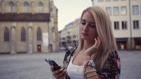 Het aantrekkelijke blondemeisje neemt haar hoofdtelefoons, aanzet de muziek in het historische stadscentrum Modieus, jong stock video