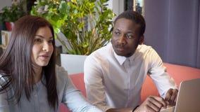 Het aantrekkelijke brunette spreekt actief met partner, terwijl Afrikaanse manat privé vergadering in restaurant stock footage