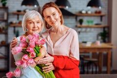 Het aantrekkelijke dochter stellen met silver-haired moeder met tulpenboeket royalty-vrije stock fotografie