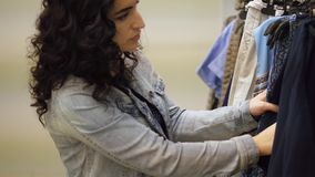 Het aantrekkelijke donkerbruine meisje kiest kleren op hangers Het mooie vrouwenbrunette koopt kleding in opslag Mooie dame met stock video