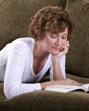 Het aantrekkelijke donkerbruine vrouw ontspannen op laag met boek Royalty-vrije Stock Afbeelding