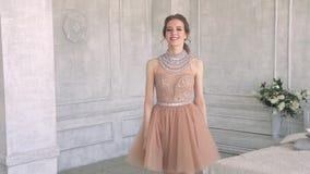 Het aantrekkelijke en leuke meisje gaat in een mooie kleding stock video