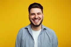 Het aantrekkelijke gebaarde jonge mens luid lachen uit, ruim glimlachend die, zijn witte rechte tanden tonen tegen geel royalty-vrije stock foto's