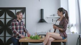 Het aantrekkelijke gebaarde mannetje bereidt heerlijke gezonde salade van verse groenten voor en greens en het wijfje zitten op l stock videobeelden