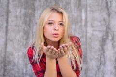 Het aantrekkelijke gelukkige meisje met blondehaar, grote lippen, met perfecte huid en maakt omhoog het verzenden van luchtkus Zi stock fotografie