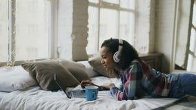 Het aantrekkelijke gemengde rasmeisje luistert aan muziek terwijl het surfen van sociale media die op laptop op bed liggen stock footage