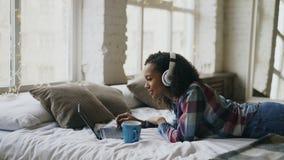 Het aantrekkelijke gemengde rasmeisje luistert aan muziek terwijl het surfen van sociale media die op laptop op bed liggen Stock Afbeelding