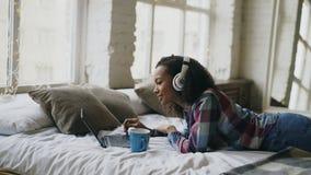 Het aantrekkelijke gemengde rasmeisje luistert aan muziek terwijl het surfen van sociale media die op laptop op bed liggen Royalty-vrije Stock Afbeelding