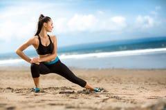 Het aantrekkelijke geschikte vrouw uitrekken zich op strand Royalty-vrije Stock Afbeelding