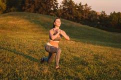 Het aantrekkelijke geschiktheidsvrouw praktizeren in het park op het gras Het Stock Foto