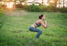 Het aantrekkelijke geschiktheidsvrouw praktizeren in het park op het gras Sh Stock Foto