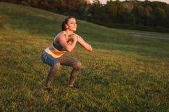 Het aantrekkelijke geschiktheidsvrouw praktizeren in het park op het gras Sh Royalty-vrije Stock Fotografie