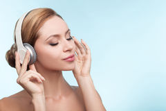 Het aantrekkelijke gezonde meisje ontspant met oortelefoons stock fotografie