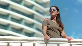 Het aantrekkelijke glimlachen looide vrouw die zonnebril dragen ontspannend op balkon van luxe modern hotel stock footage