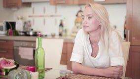 Het aantrekkelijke glimlachende blonde gekleed in wit overhemd zit bij lijst in keuken stock video