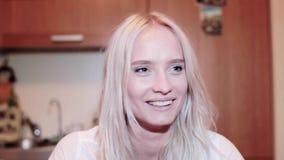 Het aantrekkelijke glimlachende blondemeisje met nieuwsgierig gezicht staart met grote bruine ogen stock footage