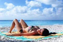 Het aantrekkelijke grilzon looien op een tropisch strand Stock Afbeeldingen
