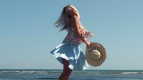 Het aantrekkelijke het strohoed van de blondeholding spinnen op strand stock video