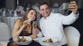 Het aantrekkelijke houdende van paar neemt selfie met champagneglazen gebruikend smartphone terwijl het hebben van diner in resta stock footage