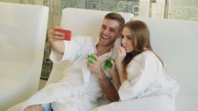 Het aantrekkelijke houdende van paar neemt selfie met cocktailglazen gebruikend smartphone terwijl het ontspannen in kuuroordsalo stock footage