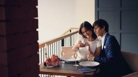 Het aantrekkelijke houdende van paar neemt selfie met smartphone terwijl het hebben van diner in restaurant De jongeren glimlacht stock video
